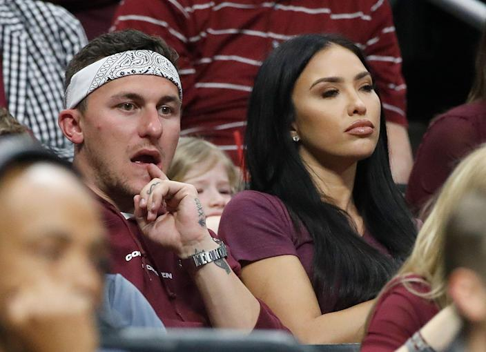 Former Texas A&M quarterback Johnny Manziel, left, and his wife, Bre Manziel, watch the second half of an NCAA men's college basketball tournament regional semifinal between Michigan and Texas A&M on Thursday, March 22, 2018, in Los Angeles. (AP Photo/Jae Hong)