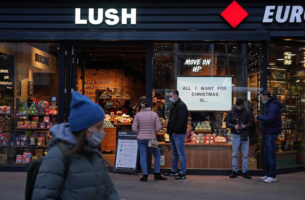 Shoppers wait to enter a Lush cosmetics store with a Christmas theme on Black Friday weekend during the second wave of the coronavirus pandemic on November 28, 2020 in Berlin, Germany.