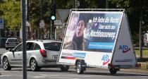 FILE - In this Wednesday, Aug. 25, 2021 file photo a car pulls an election poster for the right wing party 'Alternative for Germany' (AfD) at a street in Duesseldorf, Germany. Migration is a side issue in this year's German election campaign, but that hasn't stopped the country's biggest far-right party from trying to play it up. (AP Photo/Martin Meissner)