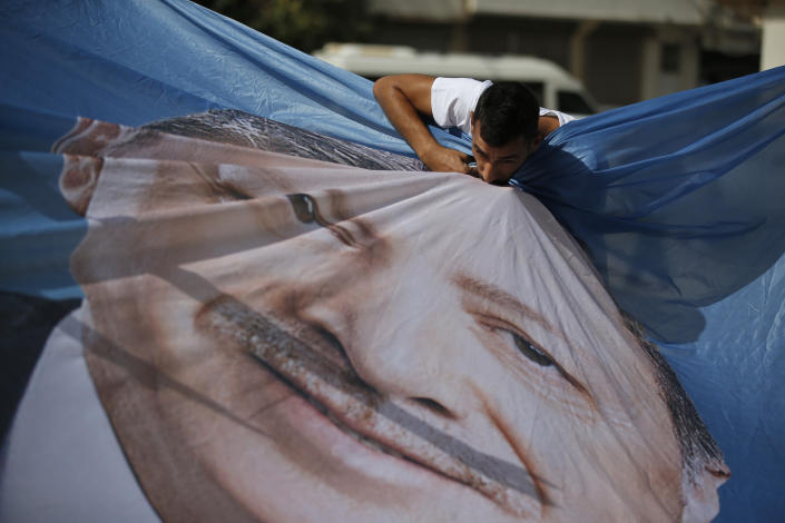 A man kisses a banner showing Turkey's President Recep Tayyip Erdogan during show of support by about a dozen people for Turkey's operation in Syria, in the border town of Akcakale, Sanliurfa province, southeastern Turkey, on Oct. 14, 2019. Erdogan has criticized NATO allies which are looking to broaden an arms embargo against Turkey over its push into northern Syria. (Photo: Lefteris Pitarakis/AP)