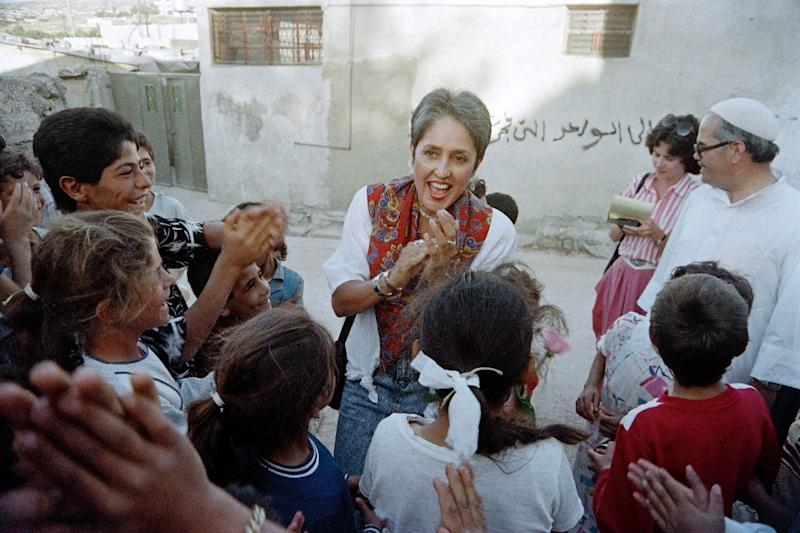 US folk singer and activist Joan Baez claps with Palestinian children of Jalazone refugee camp, on May 12, 1988, near Ramallah, during a visit to the West Bank (AFP Photo/ESAIAS BAITEL)