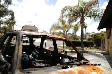 A burned car in the driveway of a suburban home that was the site of a hash oil extraction laboratory explosion is seen in the Mira Mesa area of San Diego