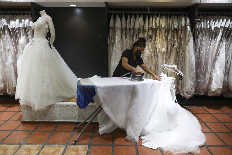 A woman wearing a mask to curb the spread of the new coronavirus irons a wedding dress at a store in Mexico City, Tuesday, June 30, 2020. (AP Photo/Eduardo Verdugo)