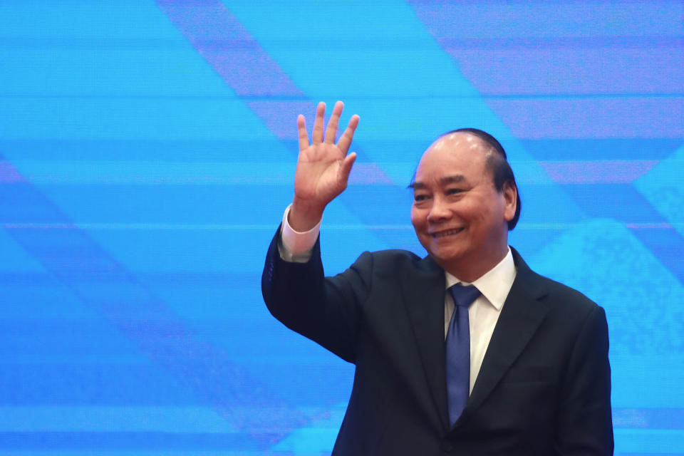 Vietnamese Prime Minister Nguyen Xuan Phuc waves after concluding the signing ceremony of the Regional Comprehensive Economic Partnership, or RCEP, trade agreement in Hanoi, Vietnam on Sunday, Nov. 15, 2020. China and 14 other countries agreed Sunday to set up the world's largest trading bloc, encompassing nearly a third of all economic activity, in a deal many in Asia are hoping will help hasten a recovery from the shocks of the pandemic. (AP Photo/Hau Dinh)