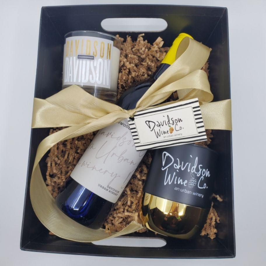 """<p><strong>Davidson Wine Co.</strong></p><p>www.davidsonwineco.com</p><p><strong>$50.00</strong></p><p><a href=""""https://davidsonwineco.square.site/product/custom-gift-basket-white-wine-candle-tumbler/23?cs=true&cst=custom"""" rel=""""nofollow noopener"""" target=""""_blank"""" data-ylk=""""slk:Shop Now"""" class=""""link rapid-noclick-resp"""">Shop Now</a></p><p>This North Carolina-based wine company actually has quite a few solid gifts for all of your wine-loving friends (yes, punny tees included), but you really can't go wrong with the white wine and candle combo. </p>"""