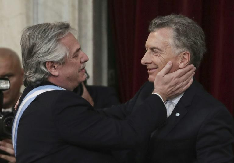 "After being sworn President Alberto Fernandez twice gave his predecessor Mauricio Macri (R) a lingering hug before vowing to ""overcome the rancor and hate"" of political polarization"