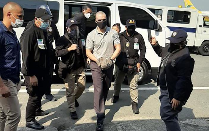 Joseph Scott Pemberton is escorted by immigration officers and US personnel as he arrives at the airport in Manila - AFP