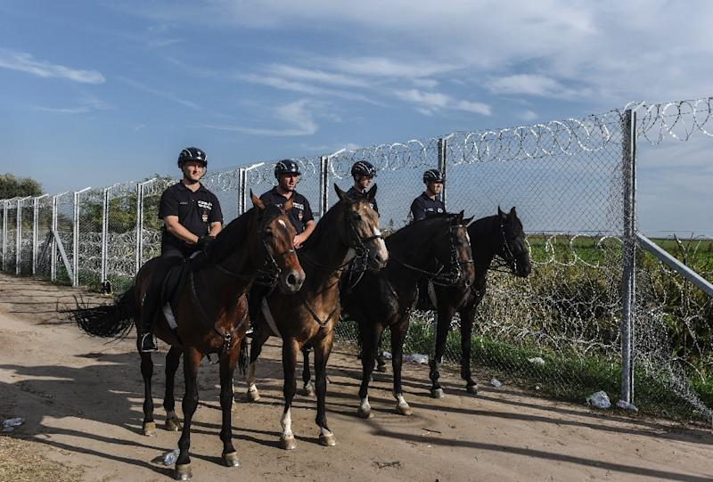 Hungarian police patrol the fence on the Hungarian-Serbian border near the town of Horgos on September 14, 2015 as they closed off the main crossing point for thousands of migrants entering from Serbia every day (AFP Photo/Armend Nimani)