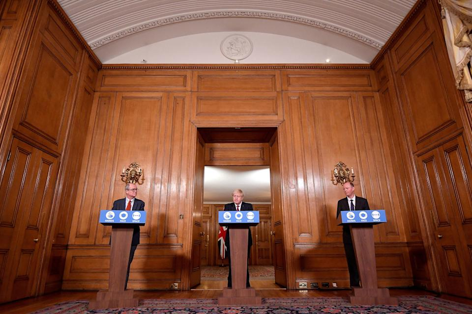 Britain's Prime Minister Boris Johnson (C), Britain's Chief Medical Officer for England Chris Whitty (R) and Britain's Chief Scientific Adviser Patrick Vallance attend a virtual press conference inside 10 Downing Street in central London on December 19, 2020. - British Prime Minister Boris Johnson on Saturday announced a