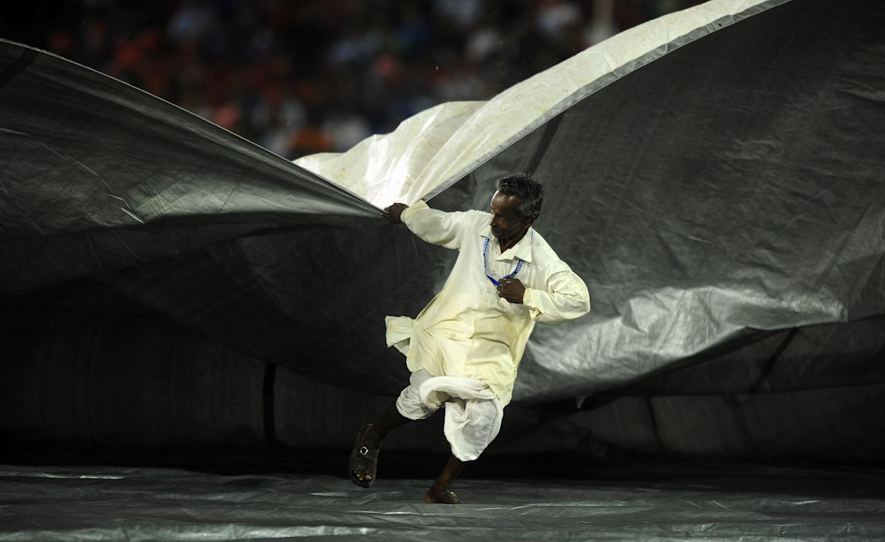 A groundsman pulls the covers as the IPL Twenty20 cricket match between Deccan Chargers and Kolkata Knight Riders is delayed due to rain at The Barabati Stadium in Cuttack on April 22, 2012.
