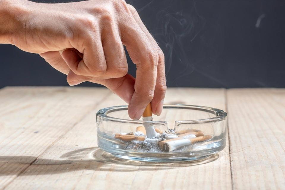 Hand stubbed out cigarette in a transparent ashtray on wooden table