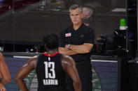 Oklahoma City Thunder head coach Billy Donovan, rear, looks onto the court as Houston Rockets' James Harden (13) walks by during the second half of an NBA first-round playoff basketball game in Lake Buena Vista, Fla., Wednesday, Sept. 2, 2020. (AP Photo/Mark J. Terrill)