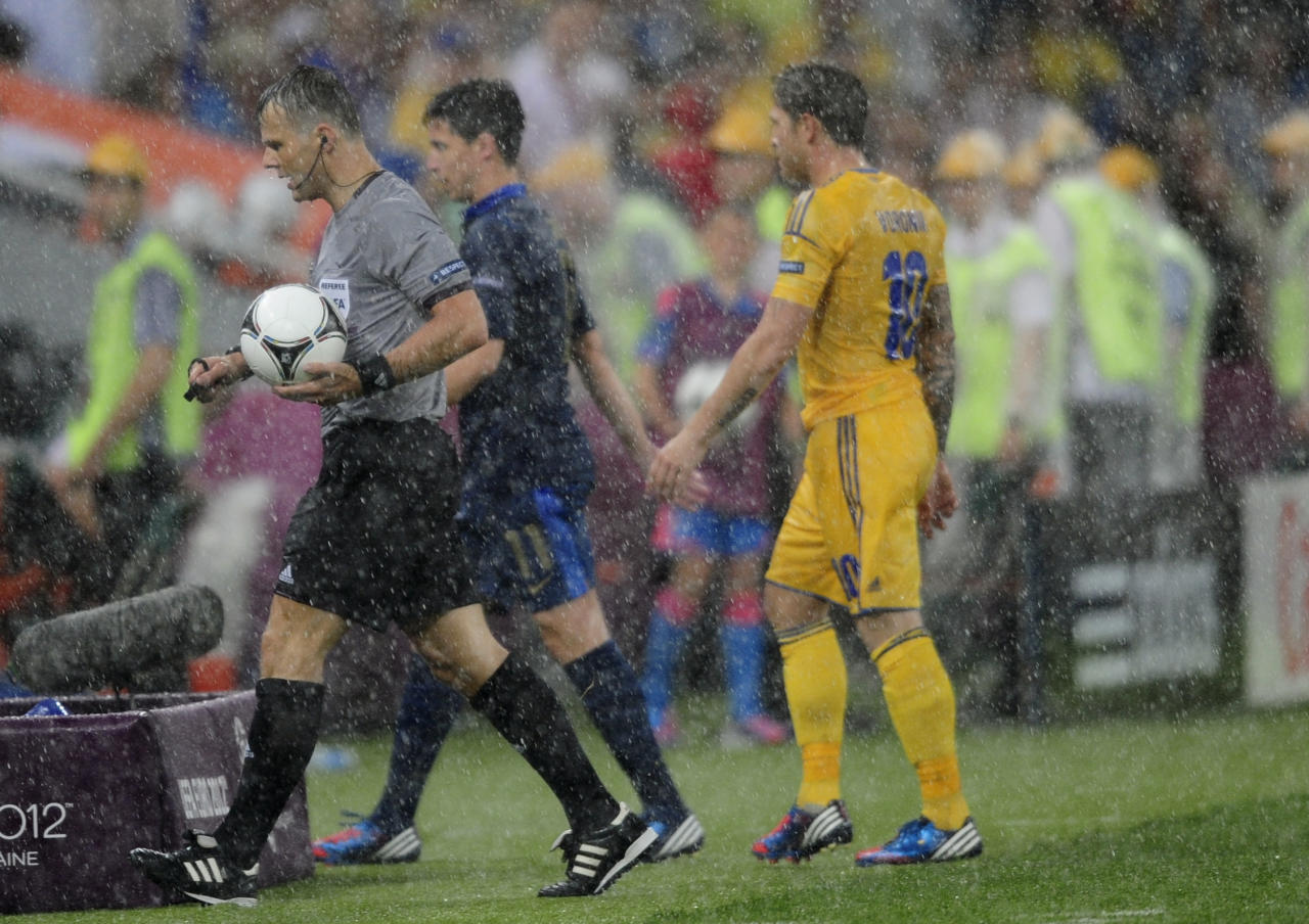 Dutch referee Bjoern Kuipers, left, and players leave the pitch after the Euro 2012 soccer championship Group D match between Ukraine and France was suspended due to heavy rain in Donetsk, Ukraine, Friday, June 15, 2012. (AP Photo/Manu Fernandez)