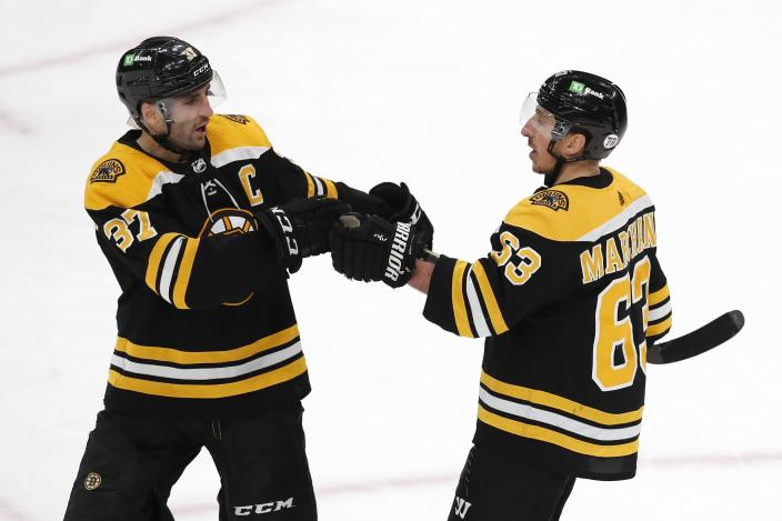 Boston Bruins' Brad Marchand (63) celebrates his open-net goal with Patrice Bergeron (37) during the third period of an NHL hockey game against the Washington Capitals, Sunday, April 18, 2021, in Boston. (AP Photo/Michael Dwyer)