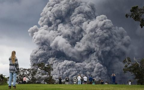 eople watch at a golf course as an ash plume rises in the distance from the Kilauea volcano - Credit:  Mario Tama/ Getty