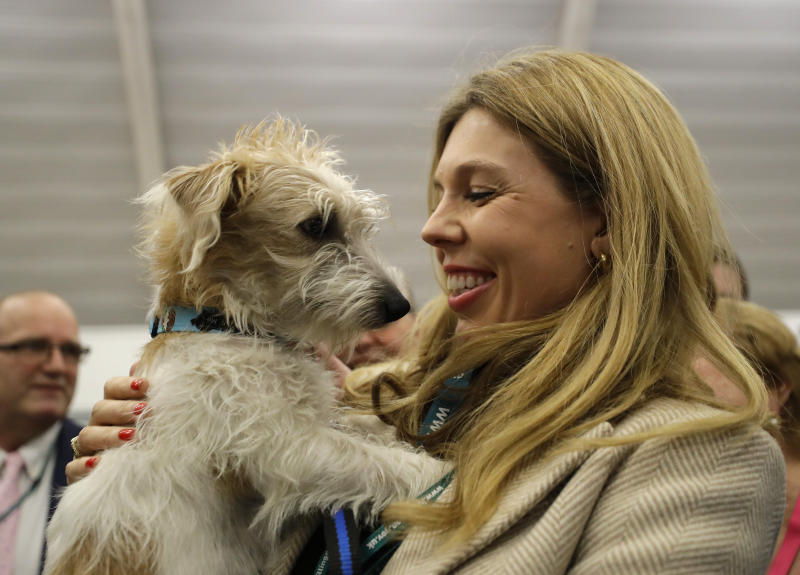 Carrie Symonds, the partner of Britain's Prime Minister and Conservative Party leader Boris Johnson holds their dog Dilyn after arriving for the Uxbridge and South Ruislip constituency count declaration at Brunel University in Uxbridge, London, Friday, Dec. 13, 2019. (AP Photo/Kirsty Wigglesworth)