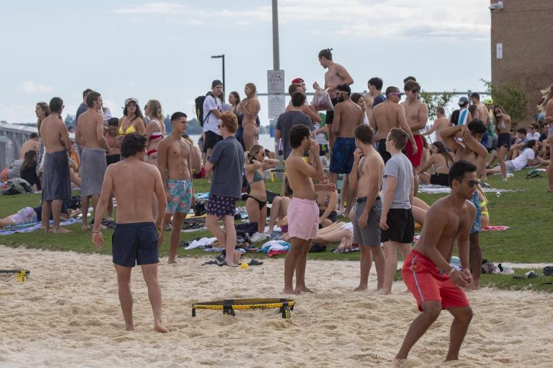 A group of young adults at the beach with young men playing beach volleyball in the foreground.
