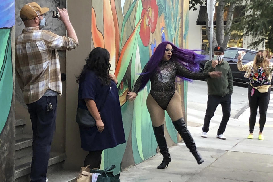 "This Friday, Aug. 28, 2020, photo shows Amoura Teese, center, performing on a sidewalk for customers in San Francisco. A San Francisco drag show night club has taken the show on the road after having to close its doors due to the coronavirus pandemic. Oasis' ""Meals on Heals"" is dispatching drag queens to deliver food, custom cocktails and socially-distant lip synch performances. (AP Photo/Haven Daley)"