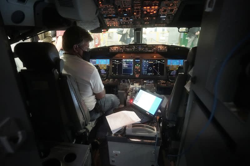 A worker loads new software into the Boeing 737 Max airplane in a maintenance hanger in Tulsa