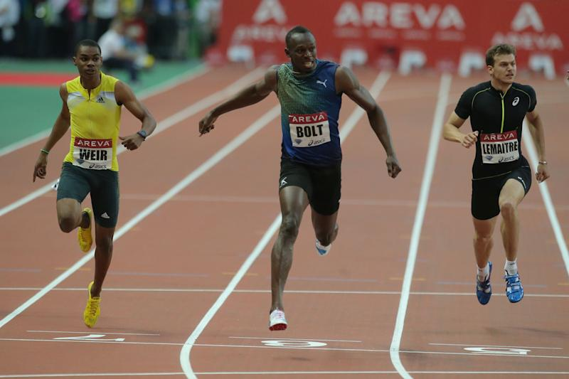 Usain Bolt of Jamaica, center, wins the Men's 200m ahead of Warren Weir of Jamaica, left, and Christophe Lemaitre of France during the Athletics Diamond League meeting at Stade de France stadium in Saint Denis north of Paris, Saturday July 6, 2013. (AP Photo/Michel Euler)