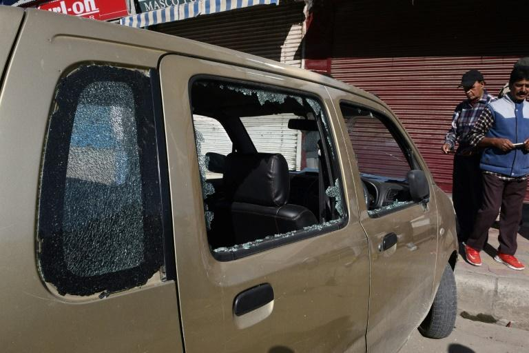 A car with broken windows is seen near the site of a grenade attack, which Indian police said injured seven people, in a market area near the old town in Srinagar