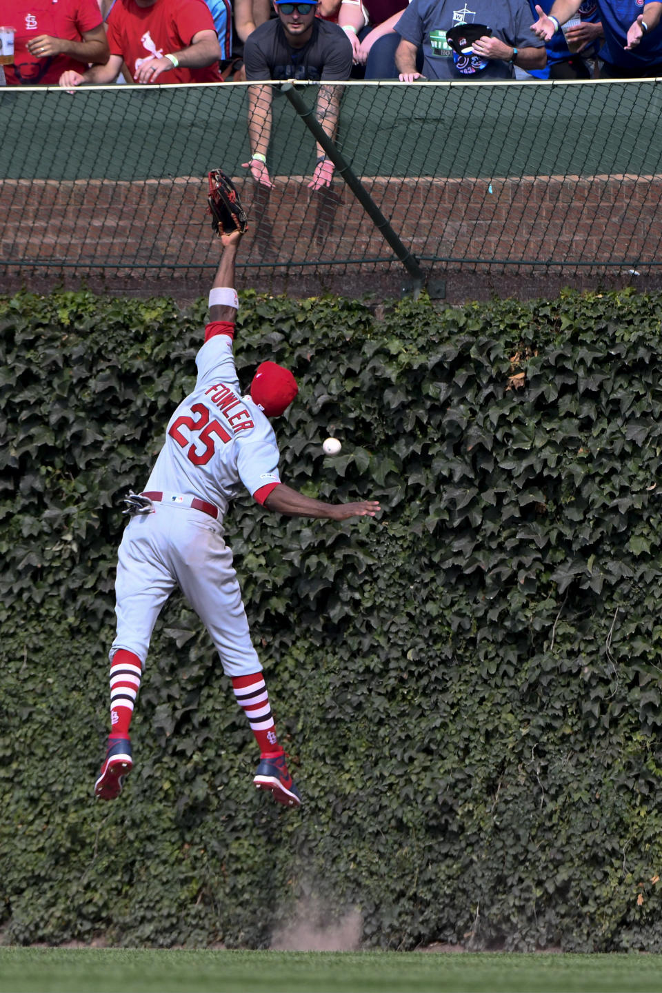 St. Louis Cardinals right fielder Dexter Fowler (25) tries to make a play on the ball hit by Chicago Cubs' Nicholas Castellanos during the fifth inning of a baseball game Friday, Sept. 20, 2019, in Chicago. (AP Photo/Matt Marton)