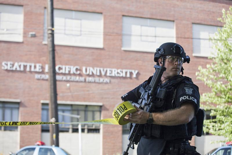 A policeman secures the scene at Seattle Pacific University after the campus was evacuated due to a shooting in Seattle, Washington June 5, 2014. A gunman opened fire on Thursday on the campus of a small Christian college in Seattle, killing one person and wounding at least three others before he was subdued by school staff and arrested, Seattle police and hospital officials said. REUTERS/David Ryder (UNITED STATES - Tags: EDUCATION CRIME LAW TPX IMAGES OF THE DAY)