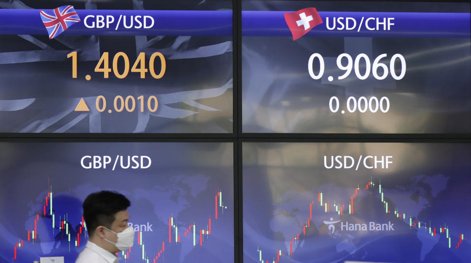 An employee of a bank walks by screens showing the foreign exchange rates at the foreign exchange dealing room in Seoul, South Korea, Friday, May 14, 2021. Asian shares rose Friday after Wall Street put the brakes on a three-day losing streak with a broad stock market rally powered by Big Tech companies and banks. (AP Photo/Lee Jin-man)