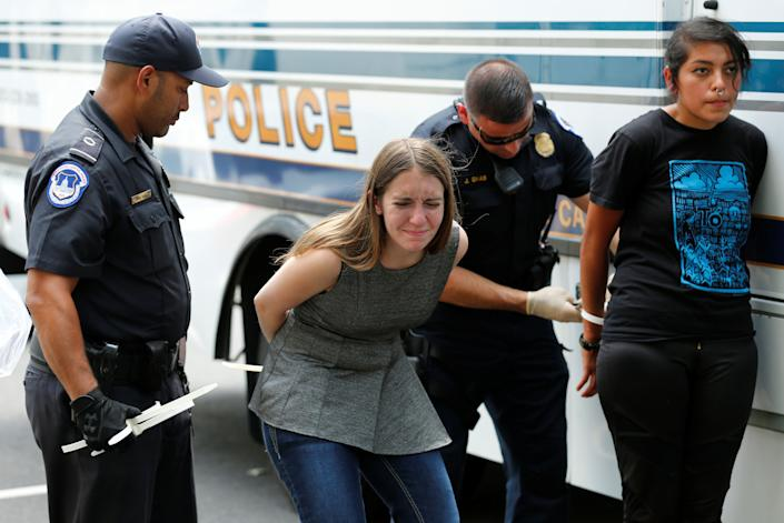 Health care activists are detained after the protest.
