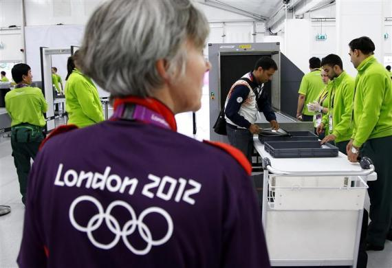 Indian shooting team member Sanjeev Rajput holds his laptop as he goes through a security check at the Welcome Center near the Athletes' Village at the Olympic Park in London July 18, 2012.