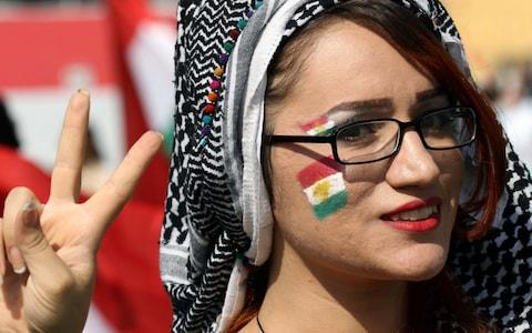 A woman flashes the V-sign as Iraqi Kurds take part in a rally to urge people to vote in the upcoming independence referendum - Credit: SAFIN HAMED/AFP/Getty Images