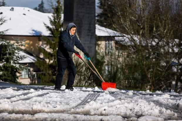 Residents and businesses in Vancouver got to work shovelling snow off sidewalks early Thursday.  (Ben Nelms/CBC - image credit)