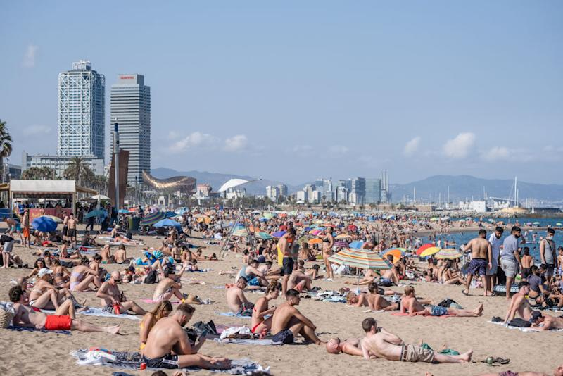 Hundreds of people are seen sunbathing at the Barceloneta beach on Saturday despite the government's warning to stay home.