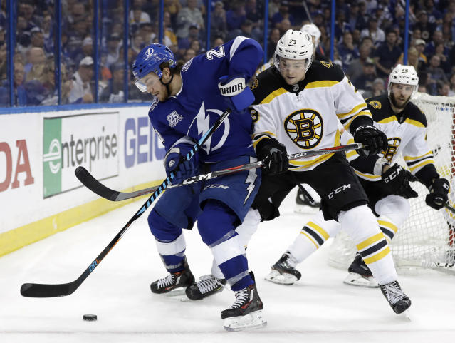 Tampa Bay Lightning center Brayden Point (21) gets tied up by Boston Bruins defenseman Charlie McAvoy (73) as they chase a loose puck during the second period of Game 2 of an NHL second-round hockey playoff series Monday, April 30, 2018, in Tampa, Fla. (AP Photo/Chris O'Meara)