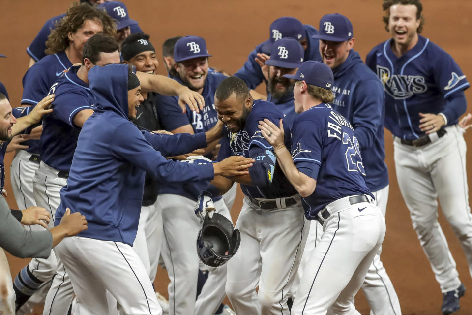 Tampa Bay Rays' Manuel Margot, center, is congratulated by teammates after his game-winning single against the Kansas City Royals during the 10th inning of a baseball game Wednesday, May 26, 2021, in St. Petersburg, Fla. The Rays won 2-1. (AP Photo/Mike Carlson)