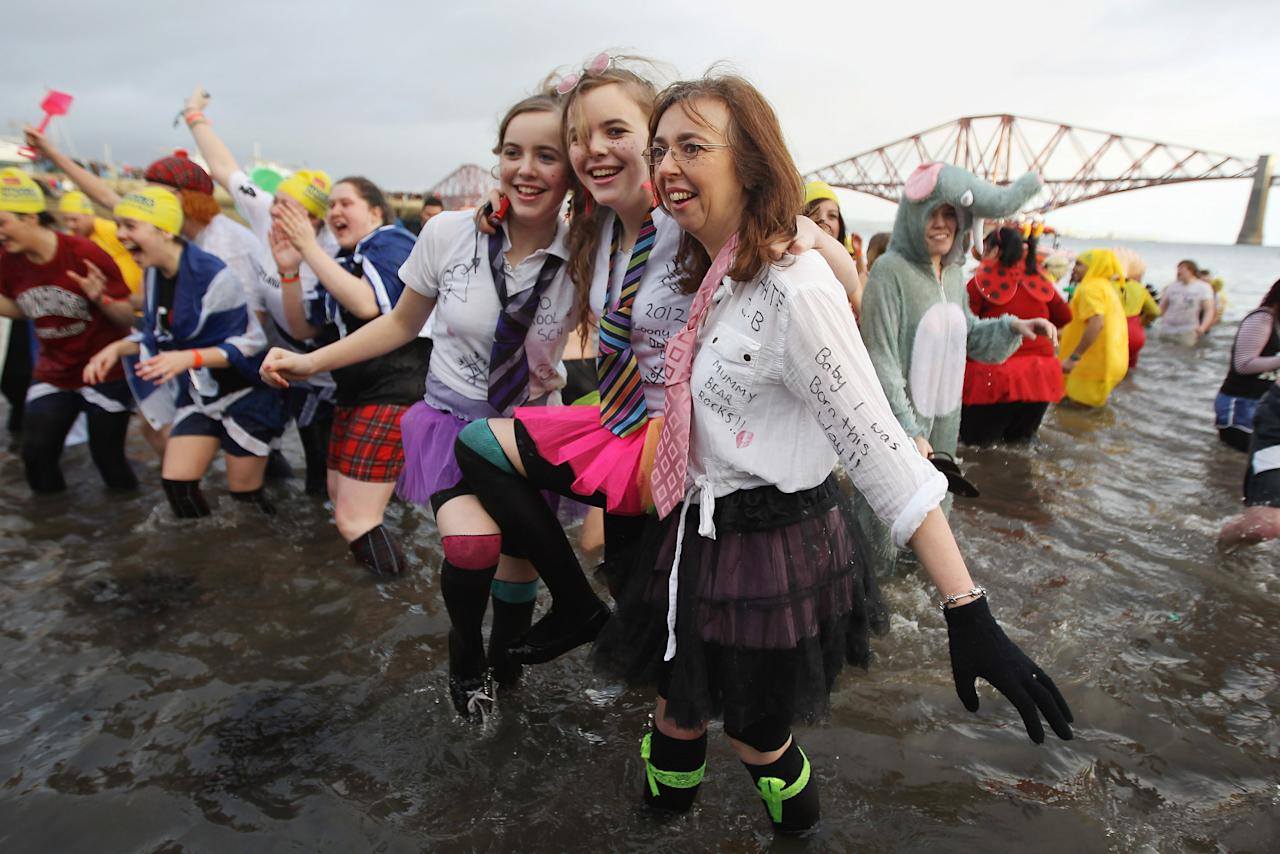 EDINBURGH, SCOTLAND - JANUARY 01:  Over 1000 New Year revellers, many in fancy dress, braved freezing conditions in the River Forth in front of the Forth Rail Bridge during the annual Loony Dook Swim on January 1, 2012 in South Queensferry, Scotland. Thousands of people gathered last night to see in the New Year at Hogmanay celebrations in towns and cities across Scotland.  (Photo by Jeff J Mitchell/Getty Images)