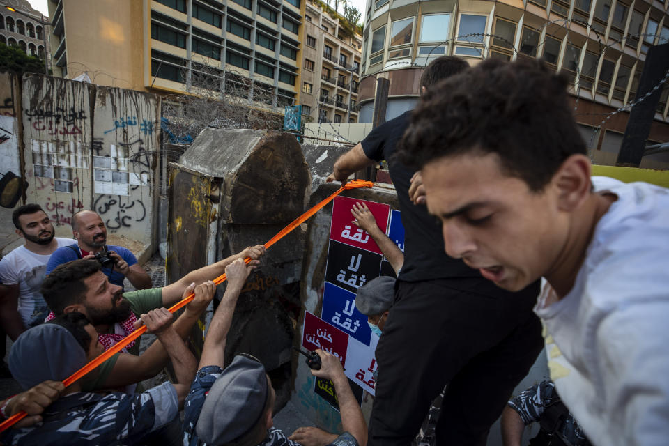 Anti-government protesters try to remove a concrete wall that was installed by security forces to prevent them from reaching the government palace in Beirut, Lebanon, Thursday, July 2, 2020. Major retailers in Lebanon announced Thursday they will temporarily close in the face of an increasingly volatile currency market and their inability to set prices while the local currency tumbles before the dollar. (AP Photo/Hassan Ammar)