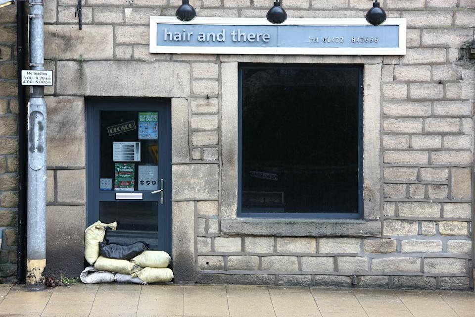 HEBDEN BRIDGE, WEST YORKSHIRE, UNITED KINGDOM - 2021/01/19: Sandbags are piled up against the door of a hair salon in Hebden Bridge on Tuesday morning as residents prepare for Storm Christoph. Residents are preparing for potential flooding as heavy rain from Storm Christoph is expected to fall onto ground which is already saturated from recent snow. (Photo by Adam Vaughan/SOPA Images/LightRocket via Getty Images)