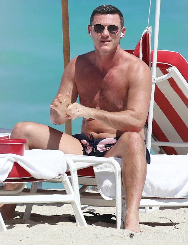 <p>Luke Evans soaks up the sun in Miami on Thursday.</p>