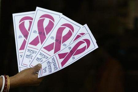 A HIV-positive woman holds AIDS awareness leaflets inside brothels in Siliguri