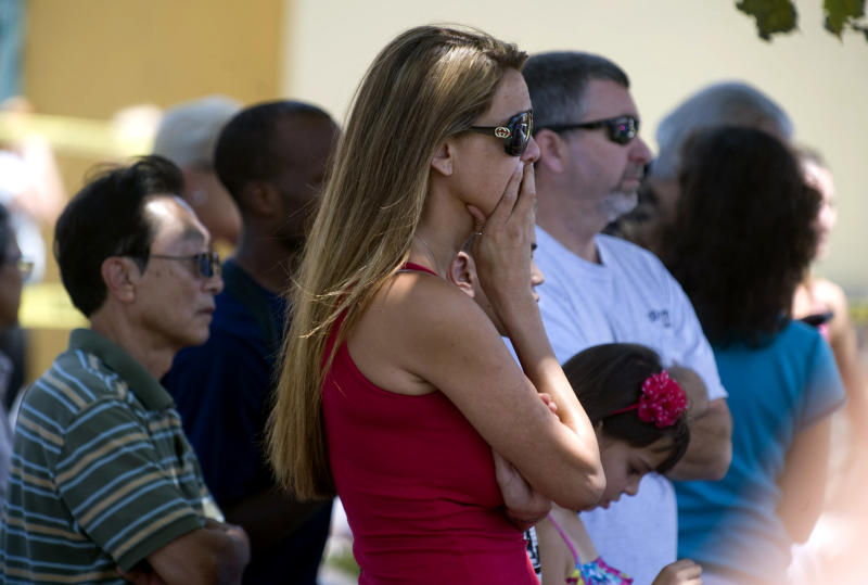 Bystanders watch as firefighters and police respond to the scene where a car crashed into the Tutoring Club in Fountain Valley, Calif., on Monday, Aug. 19, 2013. Police say a 76-year-old man drove his car into the tutoring club, injuring five people, including two who were trapped underneath the vehicle. (AP Photo/The Orange County Register, Sam Gangwer)