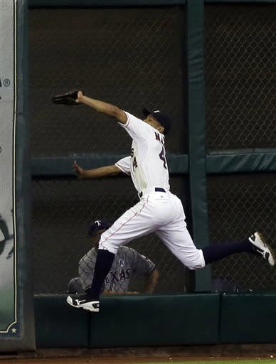 Houston Astros center fielder Justin Maxwell goes high and into the corner to make the catch and the out on Texas Rangers' David Murphy in the ninth inning of a season-opening baseball game, Sunday, March 31, 2013, in Houston. The Astros won 8-2, their 4,000th win in regular-season franchise history. (AP Photo/Pat Sullivan)