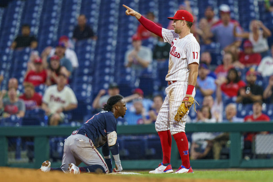 Philadelphia Phillies first baseman Rhys Hoskins, right, reacts to the throw by Jean Segura to double off Atlanta Braves' Ozzie Albies, left, at first after a lineout by Austin Riley during the third inning of a baseball game Wednesday, June 9, 2021, in Philadelphia. (AP Photo/Chris Szagola)