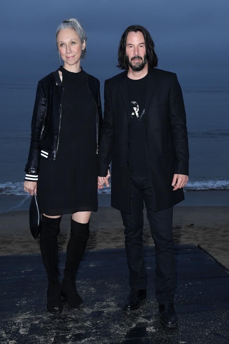 A photo of Keanu Reeves and Alexandra Grant holding hands at the Saint Laurent Mens Spring Summer '20 Show in June 2019 in Malibu.