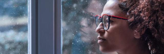 Woman looking out window with sad expression.