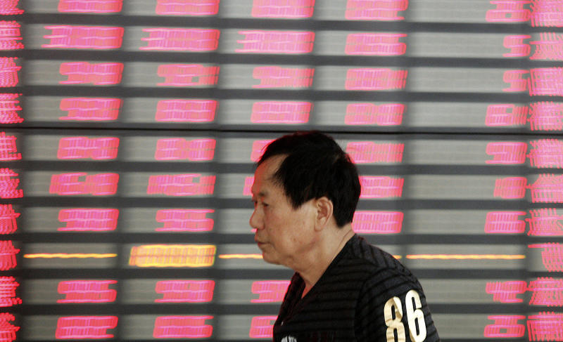 An investor walks in front of the stock price monitor at a private securities company Friday, June 29, 2012 in Shanghai, China. Asian stock markets and the euro rose sharply Friday after European leaders hammered out a strategy aimed at stanching an escalating financial crisis among the 17 countries that use the euro. (AP Photo)