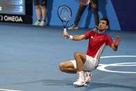 Novak Djokovic, of Serbia, falls down while returning a ball during a mixed doubles semifinals of the tennis competition at the 2020 Summer Olympics, Friday, July 30, 2021, in Tokyo, Japan. (AP Photo/Seth Wenig)