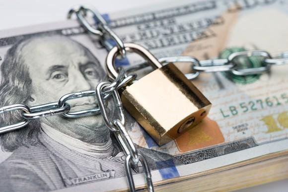 Chain and padlock wrapped around stack of hundred dollar bills