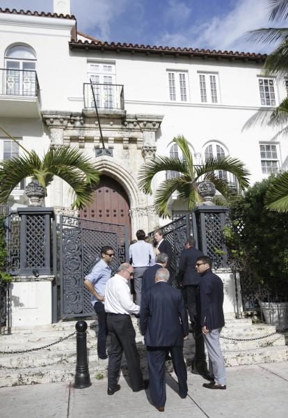 People attending the auction of the South Beach mansion that once belonged to Gianni Versace arrive at the front door, Tuesday, Sept. 17, 2013 in Miami Beach, Fla. VM South Beach LLC placed the winning bid of $41.5 million for the property. Gianni Versace bought the property in 1992. He was fatally shot on its steps in 1997 by a serial killer. His family sold it in 2000, and it operated as a private club and then as a boutique hotel until earlier this year. (AP Photo/Wilfredo Lee)