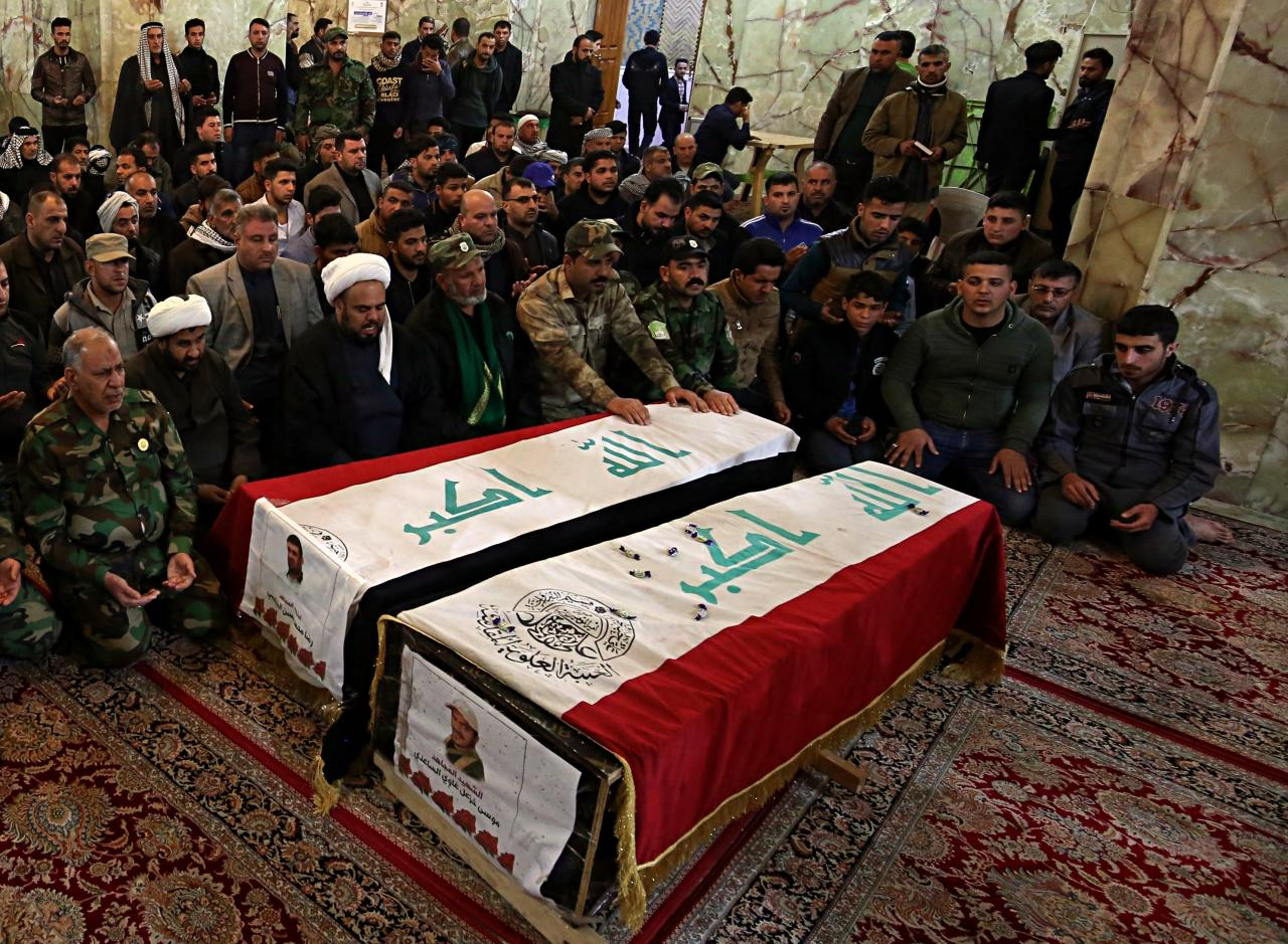 File - In this Monday, Feb. 19, 2018 file photo, mourners pray over the flag-draped coffins of two fighters of the Popular Mobilization Forces, killed during fighting against Islamic State militants, during funeral procession in Najaf, Iraq. U.S. and Iraqi officials say IS fighters facing defeat in Syria are slipping across the border into Iraq, where they are destabilizing the country's fragile security. Hundreds -- likely more than 1,000 -- IS fighters have crossed the open, desert border in the past six months. (AP Photo/Anmar Khalil, File)